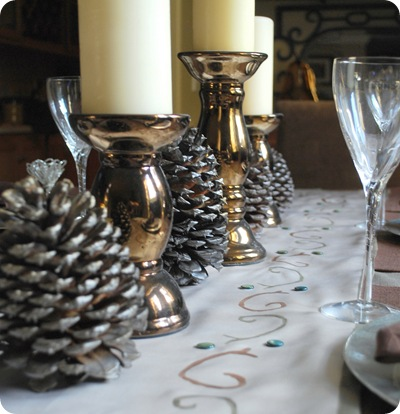 bronze candlestick and pine cones