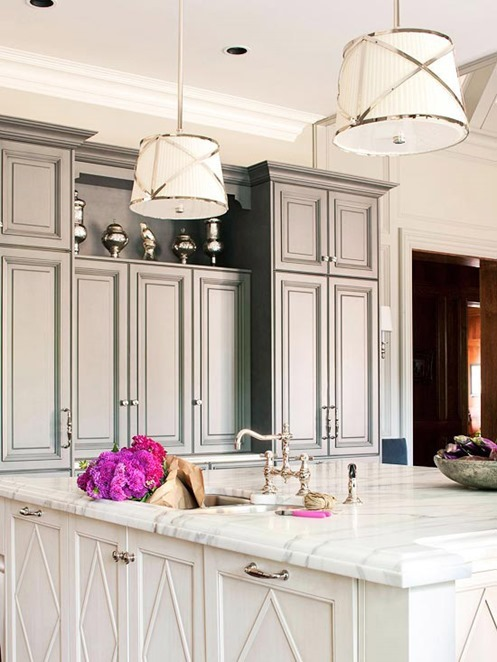 chrome pendants above marble top island bhg