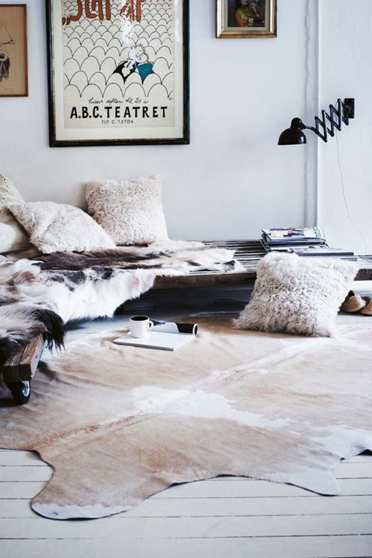 white walls cowhide rug fur pillows