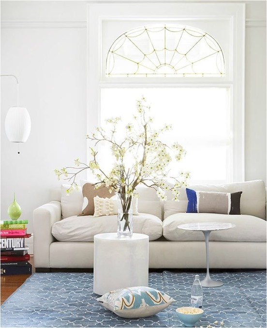 white sofa blue rug branches