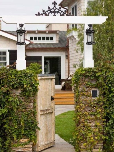 side arbor with lantern sconces bhg