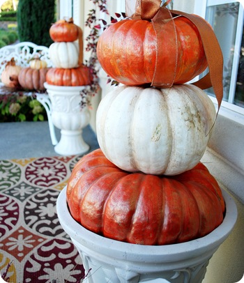 trio of pumpkins in urns from side
