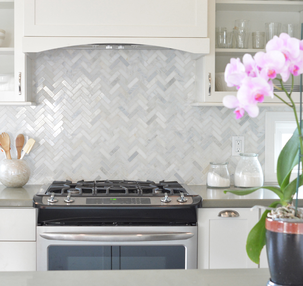 steel appliances and a classic marble herringbone backsplash
