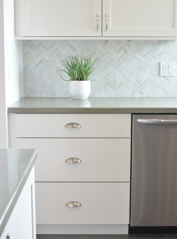 sage quartz countertop herringbone backsplash white kichen cabinets